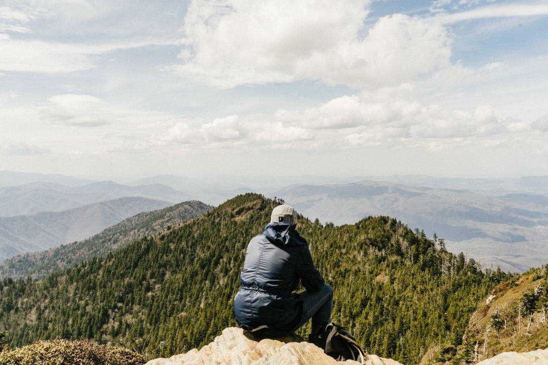 Man sits on mountain top after accomplishing hike.